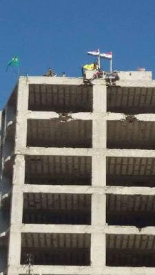 Bustan Başa semti ve Hüllük mahallesinde YPG ve rejim bayrakları.